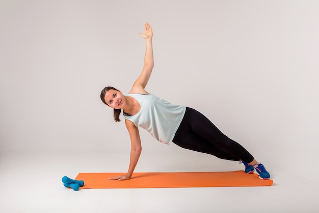 A woman makes a side plank and looks at the camera on a white with space for text
