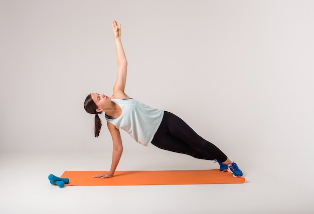 A woman makes a side plank and looks up on a white with a space for text