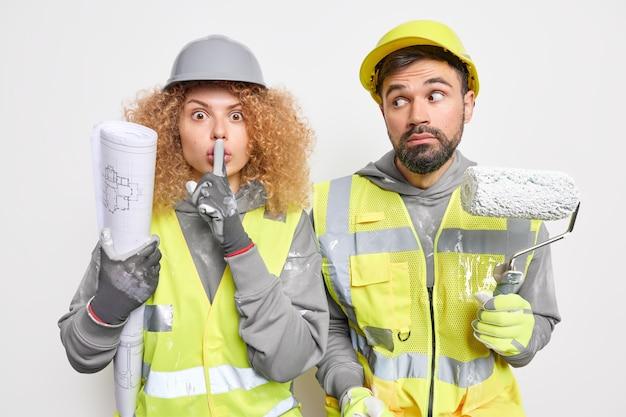 Женщина делает жест молчания держит план. шокированный ремонтник держит валик