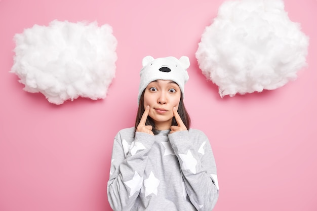 Woman makes smiles keeps fingers near corners of mouth wears soft bear hat and casual jumper looks isolated on pink
