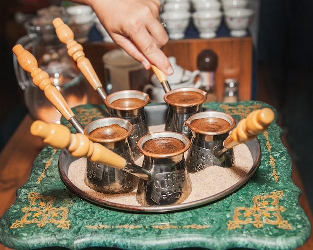 女性は、ジェズヴェに砂を入れたコーヒーマシンでトルココーヒーを作ります。オリエンタル、イーストコーヒー。
