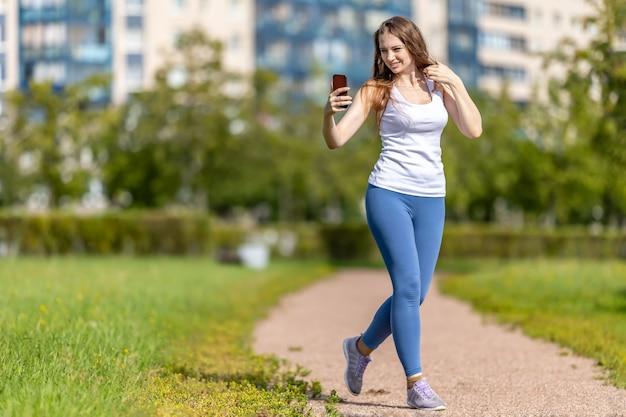 여자는 도시 정원에서 전화로 영상 통화를 합니다.