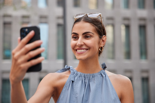 都会の環境を散歩しながらスマートフォンでビデオ通話をする女性は夏の日を楽しんでぼやけたに対して明るい気分のポーズをとる