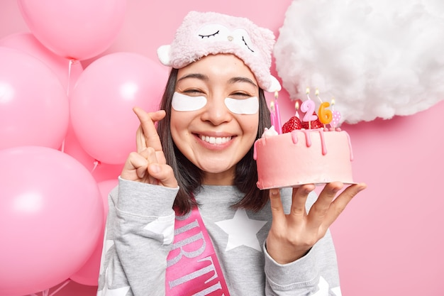 Woman makes wish before blowing candles on birthday cake crosses fingers smiles gladfully dressed in pajama celebrates birthday