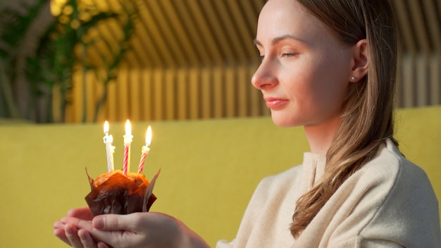 Woman makes a wish, blows out the candles on a birthday cake and laughs