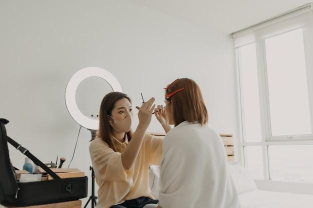 여성 메이크업 아티스트는 직장에서 그녀의 모델에게 화장을 하고 있다