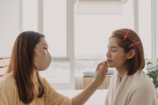 Woman makeup artist is at work and wearing makeup on her model
