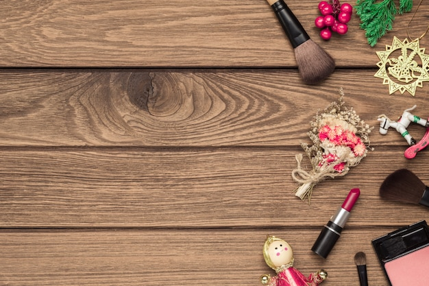 Woman makeup brushes, lipstick and christmas ornaments on wood
