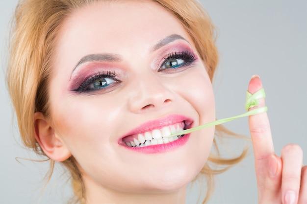 Женский макияж, жевательная резинка, резинка. портрет красивой женщины. весело женское и счастливое. крупным планом лицо, улыбка.