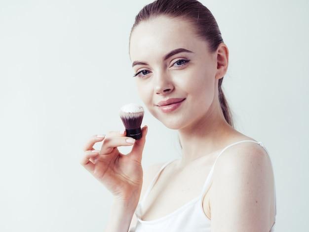 Порошок макияжа женщины прикладывая кожу лица красивый женский естественный портрет.