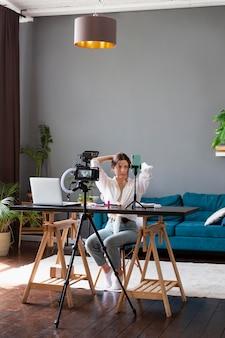 Женщина делает красоту видеоблог со своей профессиональной камерой