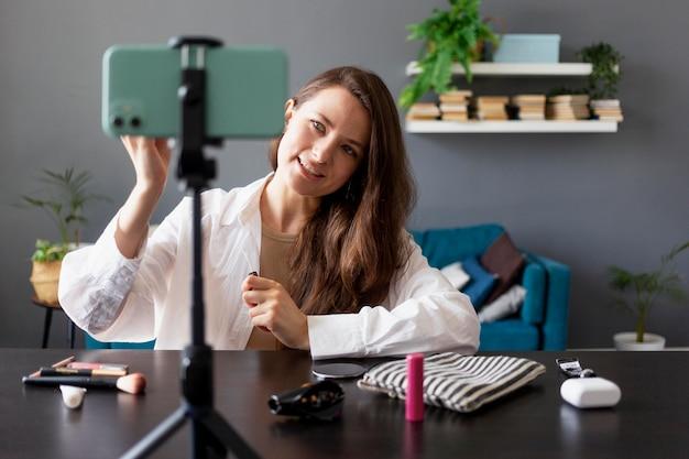 Женщина делает красоту видеоблог со своим смартфоном