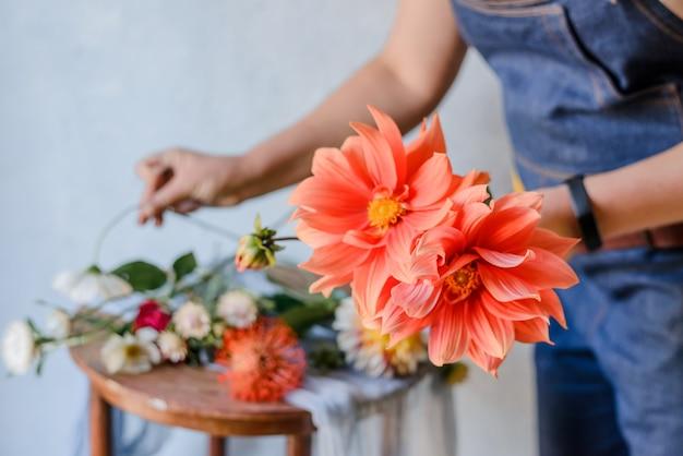 Женщина делает букет из свежих садовых пионов. создание весеннего букета. флорист работает над новым букетом.