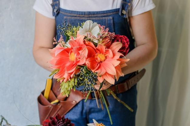 Женщина делает букет из свежих садовых пионов. создание весеннего букета с красными и оранжевыми цветами.