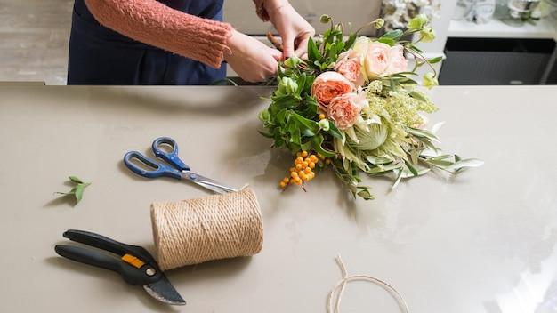 バラの花束を作る女性ダリアゴールデンデイジーとジャスミン。フラワーアレンジメントの配達。