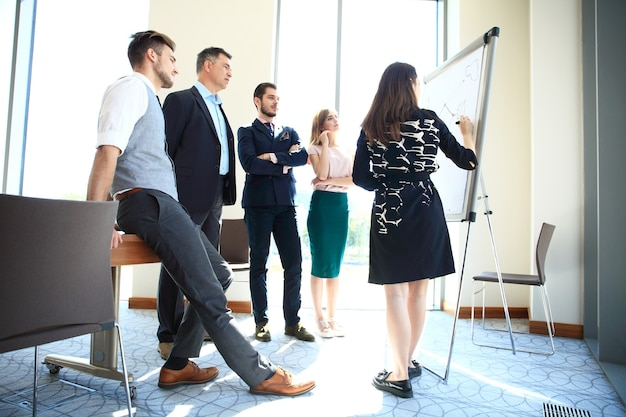 グループにビジネスプレゼンテーションを行う女性。