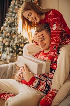 Женщина делает рождественский подарок своему парню