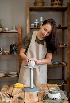 Женщина делает глиняный горшок в своей мастерской