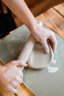 Женщина делает глиняный горшок