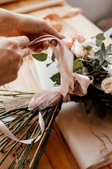 Женщина делает цветочную композицию