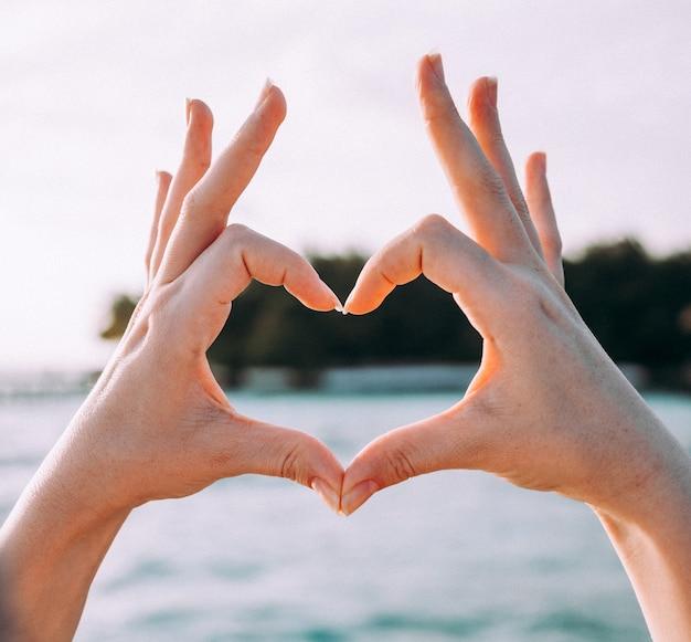 Женщина делает форму сердца руками и пальцами.