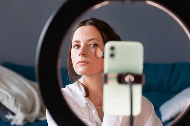 Женщина делает макияж влог со своим смартфоном