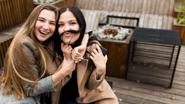 彼女の友人の隣に彼女の髪で口ひげを作る女性