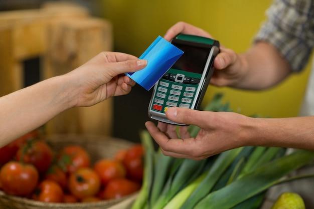 食料品店でnfcテクノロジーを使用して支払いを行う女性