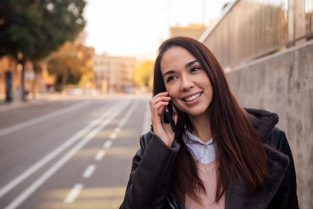 Женщина делает телефонный звонок, идя по улице