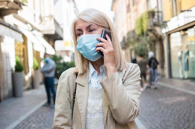 マスクをして電話をかける女性