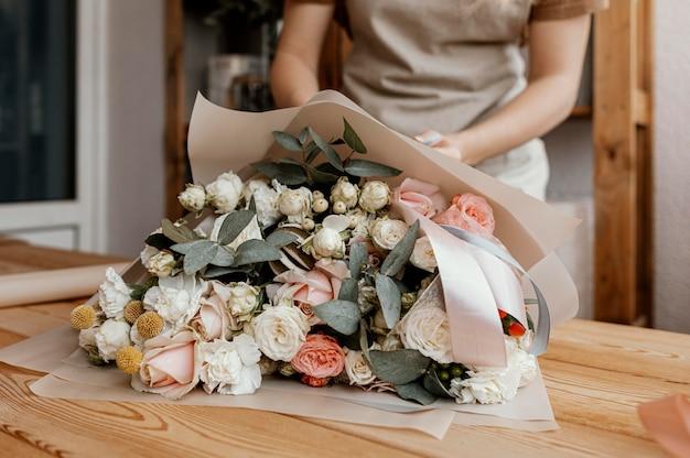 Женщина делает красивую цветочную композицию