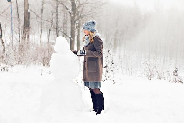 Женщина делает снеговика в зимнее время