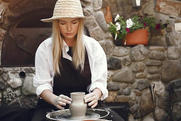 Женщина делает вазу из глины