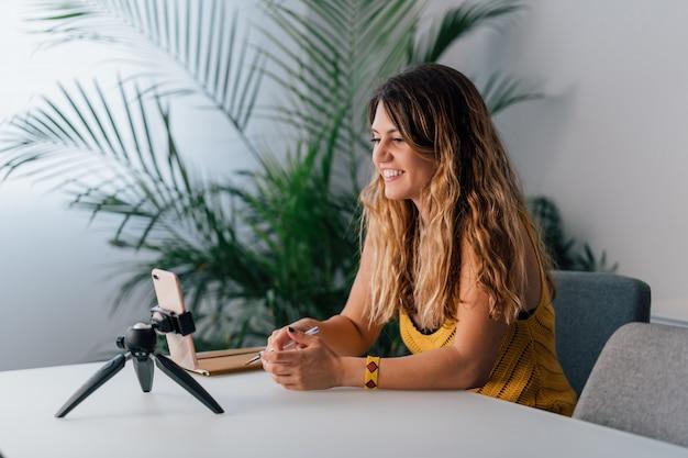 Женщина делает видео звонок с ее смартфон на дому.