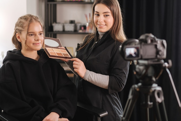 Женщина делает видео для своего блога о создании макияжа, цифровая камера на штативе. молодая женщина-блогер