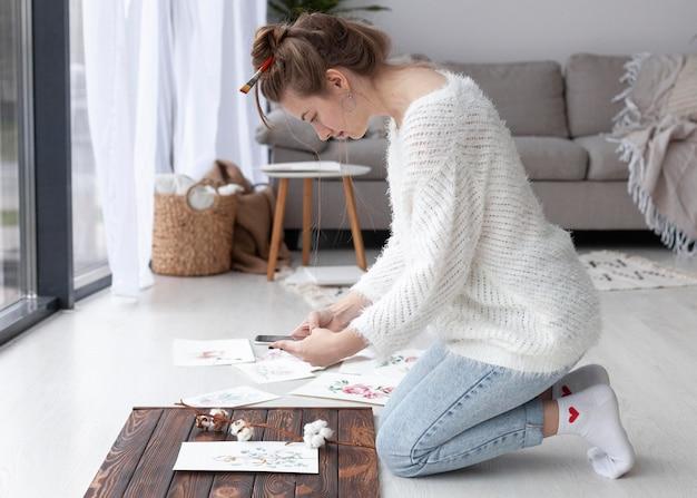 집에서 그녀의 그림 동영상 블로그를 만드는 여자