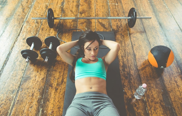 Woman making abs training on the gym floor