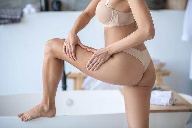 Женщина делает антицеллюлитный массаж руками