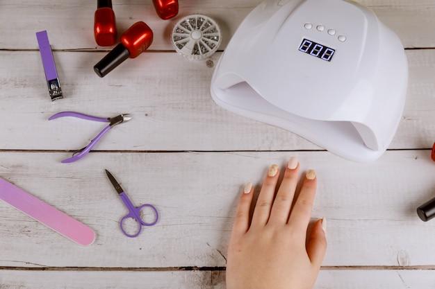Woman making beautiful acrylic manicure with led lamp