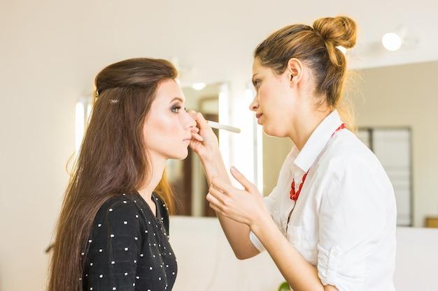 サロンで美容とメイクアップをする女性。美と人についてのコンセプト。