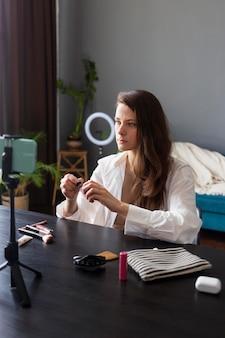 Donna che fa un vlog di bellezza con il suo smartphone