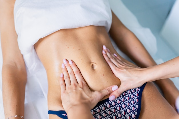 Woman making a belly massage in light procedure room.