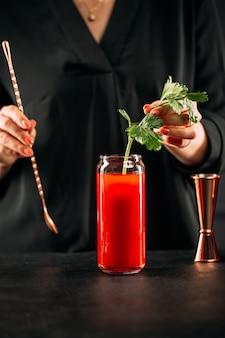セロリでブラッディマリーカクテルを作る女性