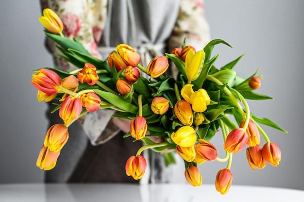 春のチューリップの花の花束を作る女性