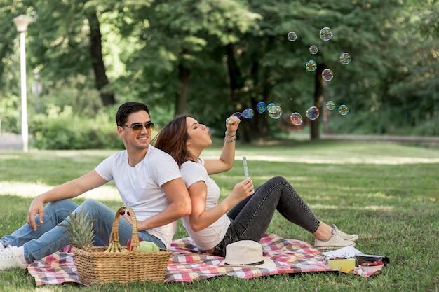 Woman making bubbles at picnic