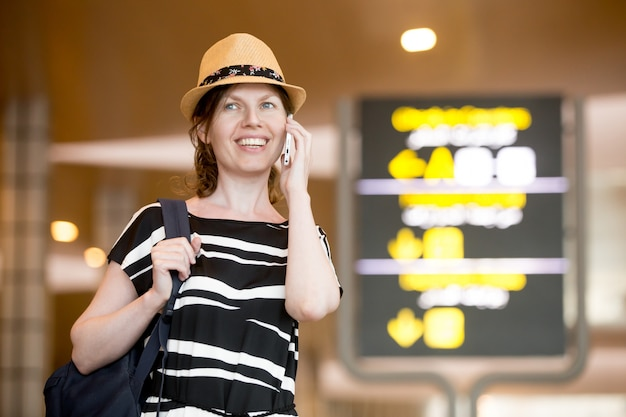 Woman making call in front of information board in airport Free Photo