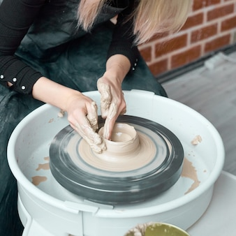 Woman making ceramic pottery on wheel