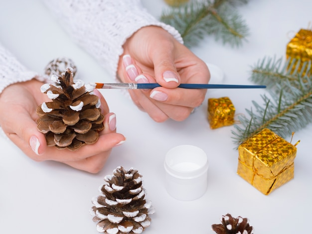 Woman making christmas decorations with pine cones