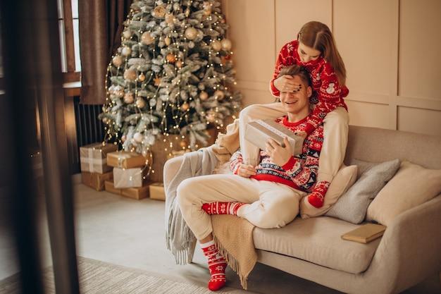 Donna che fa un regalo di natale al suo fidanzato