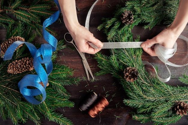 Женщина делает руки рождественский венок